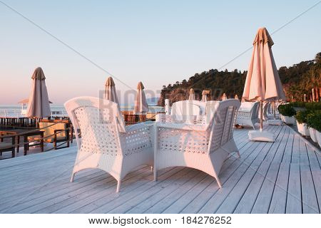 Summer restaurant on beach. Breathtaking view on mediterranean sea. White wooden terrace and braided furniture