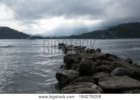 Stone pier on Phaselis bay. Overcast sky with sun rays. Drammatic scene. Located place: Kemer, Turkey.