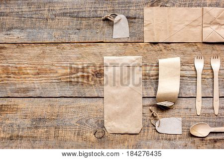 food delivery service workdesk with paper bags and flatware on restourant wooden table background top view mockup