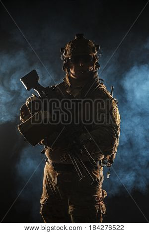 Army soldier in Combat Uniforms with machine gun, plate carrier and combat helmet are on. Studio contour silhouette shot, backlight, dark glowing smoke background