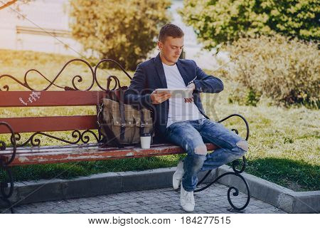 A man with a phone and tablet computer running outdoors on a sunny day