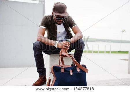 Portrait Of Sitting Stylish African American Man Wear On Sunglasses And Cap, Looking On His Watches