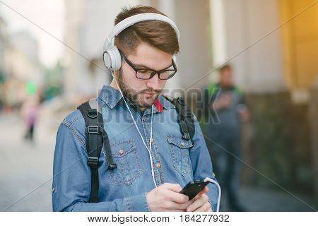 boy with headphones, phone and tablet walks in the city and park