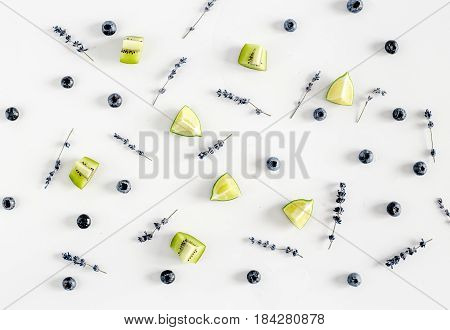 blueberry pattern with cut citrus fruit and lavander flowers on white wooden desk background top view