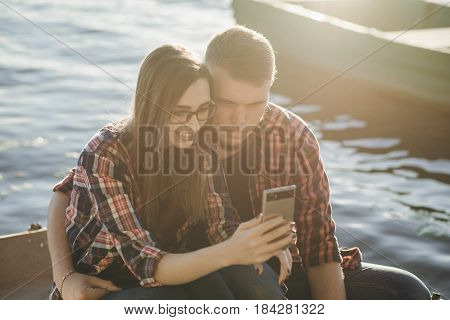 couple walks the park and the river. resting on the beach. uses communication