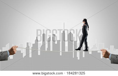 Businessman with blindfolder on eyes walking on rope
