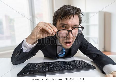 Confused Or Unsure Man Is Working With Computer And Looking At Y
