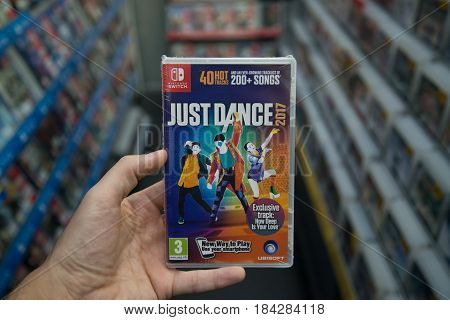 Bratislava, Slovakia, circa april 2017: Man holding Just Dance 2017 videogame on Nintendo Switch console in store