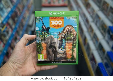 Bratislava, Slovakia, circa april 2017: Man holding Zoo Tycoon videogame on Microsoft XBOX One console in store