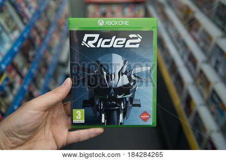Bratislava, Slovakia, circa april 2017: Man holding Ride 2 videogame on Microsoft XBOX One console in store