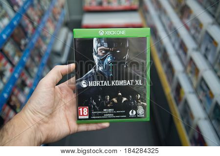 Bratislava, Slovakia, circa april 2017: Man holding Mortal Kombat XL  videogame on Microsoft XBOX One console in store