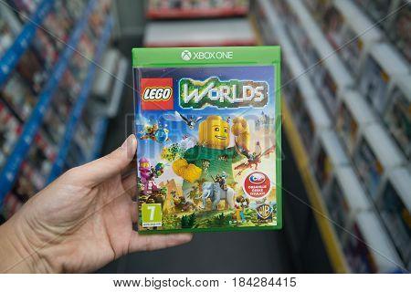 Bratislava, Slovakia, circa april 2017: Man holding Lego Worlds videogame on Microsoft XBOX One console in store