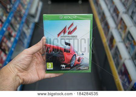 Bratislava, Slovakia, circa april 2017: Man holding Assetto Corsa videogame on Microsoft XBOX One console in store
