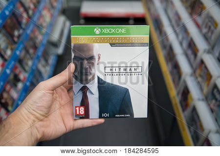 Bratislava, Slovakia, circa april 2017: Man holding Hitman the complete first season videogame on Microsoft XBOX One console in store