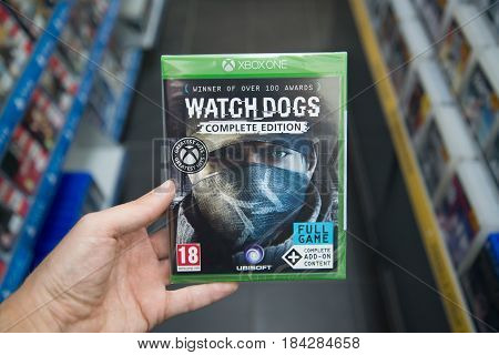 Bratislava, Slovakia, circa april 2017: Man holding Watch dogs videogame on Microsoft XBOX One console in store