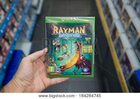 Bratislava, Slovakia, circa april 2017: Man holding Rayman legends videogame on Microsoft XBOX One console in store