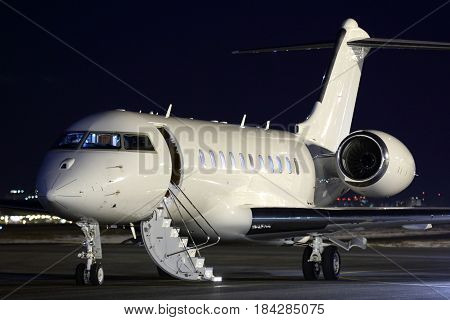 Business jet airplane standing at parking at night.