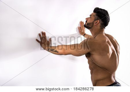 Muscular bodybuilder leaning against white wall, looking at it, with large copyspace next to him