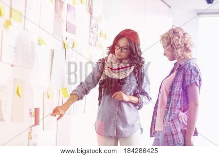 Businesswomen discussing over papers stuck on wall in creative office