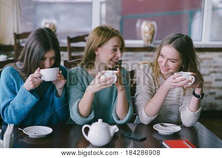 three girls sitting in a cafe at the table and drink tea