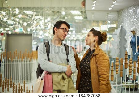 Woman speak to a man in a shopping mall, white a man looks at woman dissatisfied