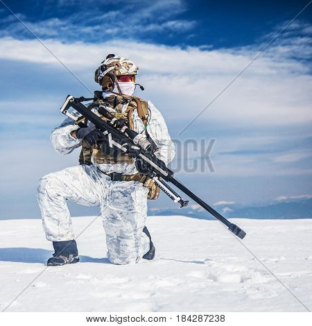 Army soldier with Sniper rifle in action in the Arctic. He wears chest rig, backpack, suffers from extreme cold, strong wind, but endures while mission continues, in snow desert
