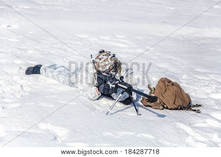 Army soldier with Sniper rifle in action in the Arctic. He lies in the snow desert, suffering from extreme cold, but waiting as long as enemies appear to kill them