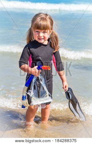 happy girl on beach with colorful face masks and snorkels sea in background.