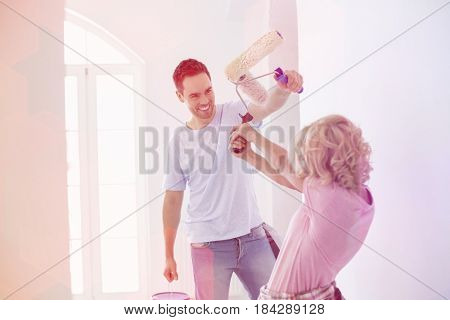 Playful couple fighting while painting new house