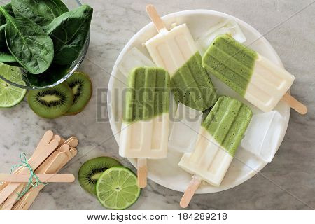 Green Smoothie Popsicles With Kiwi, Lime And Spinach On A White Marble Plate, Above View