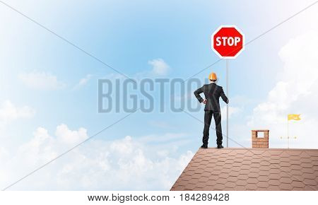 Engineer man standing on house roof and holding red prohibition sign. Mixed media