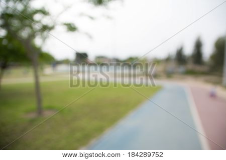 Defocused image of a park with sunshine and green leaves. Abstract blured background.