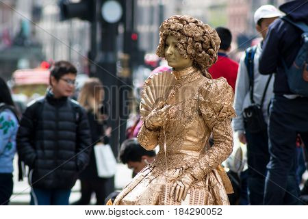London UK - April 25 2017: Street performer in London woman dressed as a golden statue on Piccadilly Circus