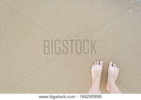 Beautiful female bare feet with pastel pedicure on the beach in sunny day. Summertime holidays concept. Top view. Copy space.