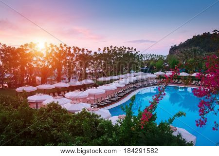 Swimming pool with sunshades and lounge chair in morning time. Amazing scene near mediterranean sea