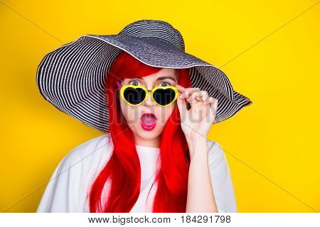Attractive Surprised Red-haired Young Woman In Sunglasses And Hat On Yellow Background