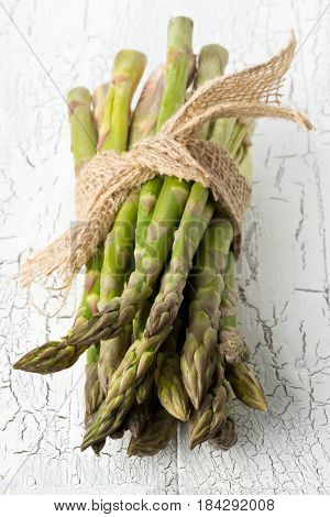 Bundle of fresh cut raw uncooked green asparagus vegetable on white rustic table background