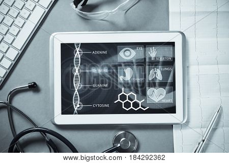 White tablet pc and doctor tools on gray surface