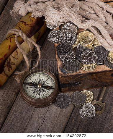 Gold and silver coins in a treaure chest with compass and map