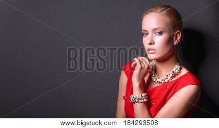 Portrait of young woman on red dress, isolated black background.