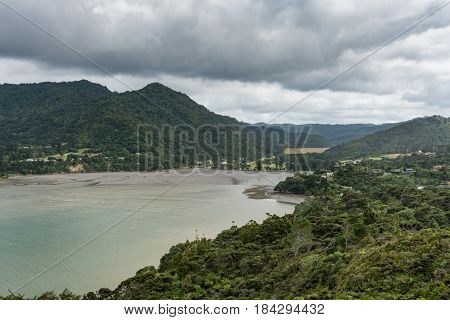 Auckland New Zealand - March 2 2017: Deep end of Huia Bay with mud flats and mountains under heavy cloudscape. Green foliage green-gray waters hidden dwellings.