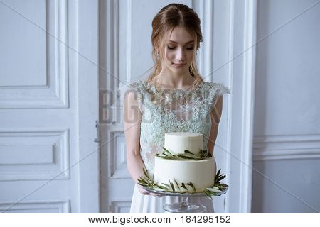 Beauty bride in bridal gown with cake and lace veil indoors. Beautiful model girl in a white wedding dress. Female portrait of cute lady with pie. Woman with hairstyle