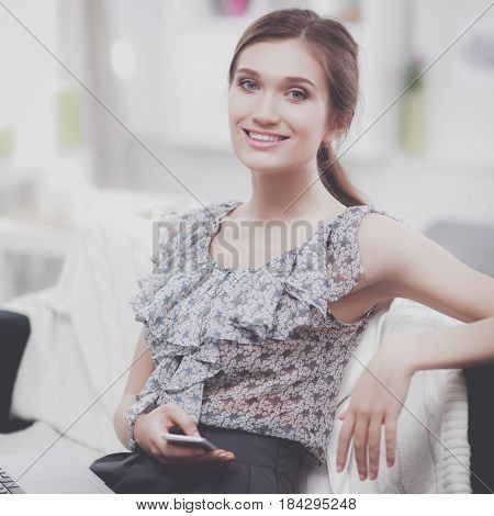 Attractive young businesswoman sitting in the office.