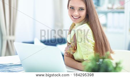 Smiling woman with documents sitting on the desk with laptop