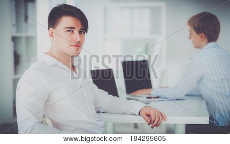 Young businessman working in office sitting at desk .