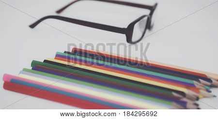 Color pencils and glasses on the desk.