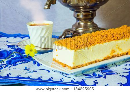 Professional bakery. Gorgeous white cheesecake, sprinkled with sweet crumbs. The background is a shiny samovar and an porcelain cup with hot tea on blue kitchen towel