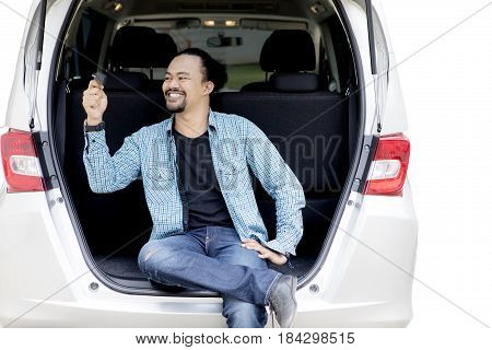 Portrait of a cheerful Afro man twisting a new car key on the back of his car