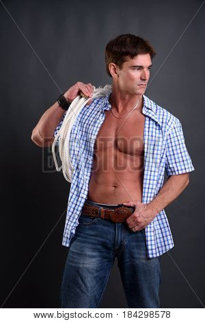 The handsome cowboy is holding a lasso.