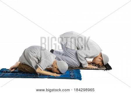 Portrait of Asian family wearing Islamic clothes while posing prostration isolated on white background